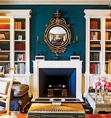 Brilliantly Pigmented Peacock Blue Walls, Contrasted By Bright Golden  Yellow Books And Accents. Gold And Black Federal Mirror.